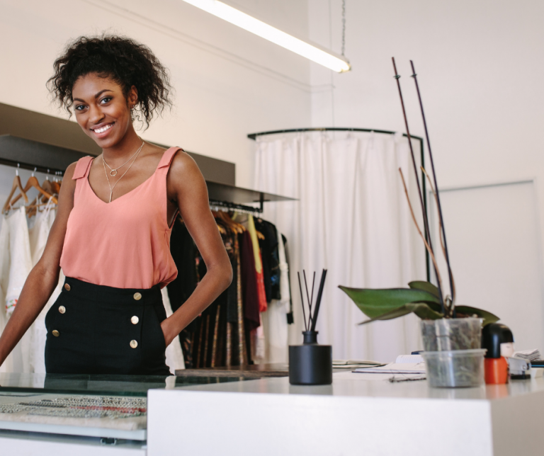 A black entrepreneur standing next to her desk in her office